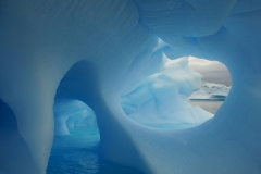 A blue iceberg floats adrift in a bay of the Antarctic Peninsula